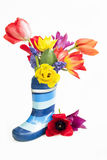 Bunch of colorful tulips and muscari placed in a waterproof boot Stock Images