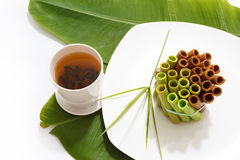 A bunch of colorful waffle rolls on a white plate. And a leaf with a cup of green tea Royalty Free Stock Images