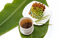 A bunch of colorful waffle rolls on a white plate. And a leaf with a cup of green tea Stock Image