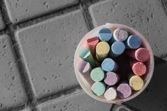 Bunch of coloring chalks in a plastic bucket Royalty Free Stock Photography