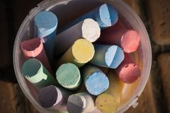 Bunch of coloring chalks in a plastic bucket Stock Photography