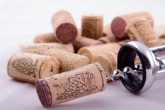 Bunch of corks and corkscrew. Bunch of corks with different designs and corkscrew in a background Royalty Free Stock Photos