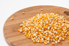 Bunch of corn for popcorn on a kitchen wooden board Royalty Free Stock Photos