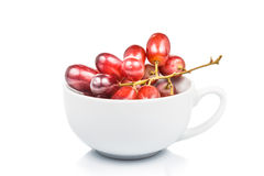 Bunch of crimson red grapes in a coffee mug Royalty Free Stock Images