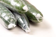 Bunch of cucumber wrapped in plastic films. Isolated on white background stock photos