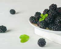 A bunch of dewberries on a white plate. Light background. A high key. Stock Image