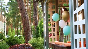 Bunch of different colorful helium air balloons playing on wind tied to wooden outdoor gazebo terrace as decoration for. Children bithday party. Anniversary stock video footage