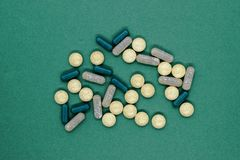 Bunch of different forms green medication pills on green background surface royalty free stock images