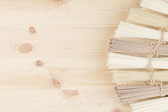 Bunch of different raw japanese noodles on wooden dish on beige board, top view. Royalty Free Stock Photography