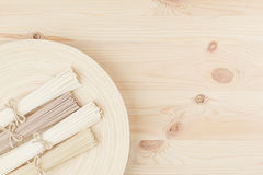 Bunch of different raw japanese noodles on wooden dish on beige board, top view. Decorative border with copy space Royalty Free Stock Images