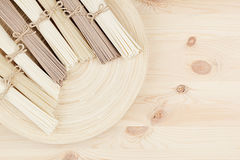 Bunch of different raw japanese noodles on wooden dish on beige board, top view. Decorative border with copy space Stock Image
