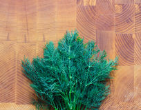 Bunch of dill on a wooden board. Green fennel on a wooden board Stock Photos