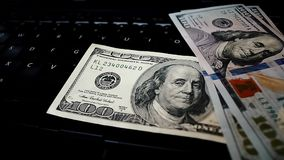 Bunch of dollar bills thrown on a laptop keyboard featured defocused bokeh. Pack of one hundred dollars notes thrown on a laptop keyboard stock video
