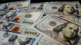 Bunch of dollar bills thrown on a laptop keyboard featured defocused bokeh. Pack of one hundred dollars notes thrown on a laptop keyboard stock footage