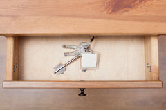 Bunch of door keys with keychain in open drawer Stock Photography