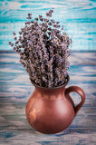 Bunch of dried lavender in a vase on a wooden table. Stock Image