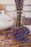 Bunch of dry cut lavender and teapot on wooden table. White bricks background. Royalty Free Stock Images