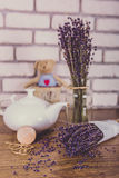 Bunch of dry cut lavender and teapot on wooden table. White bricks background. Stock Photos