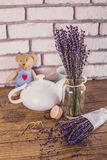 Bunch of dry cut lavender and teapot on wooden table. White bricks background. Stock Image