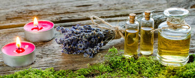 Bunch of dry lavender, candles and bottles of scented oil. Bunch of dry lavender. Candles. Glass bottles aroma essential oils or Spa or natural aromatic oil on stock image