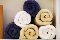 Bunch of earth tone towels in bathroom shelf. For decoration stock images