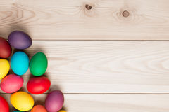 A bunch of Easter eggs in the corner and a wooden background Stock Photography
