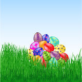 Bunch of easter eggs on the grass. Colorful bunch of Easter eggs with pattern on green grass. Different eggs on light blue background. Vector illustration. Set Stock Photos