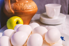 A bunch of eggs on the plate, still life. With apples and pitcher Royalty Free Stock Photos