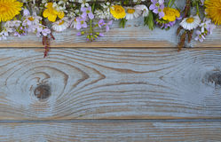 Bunch of fieldflowers,daisies, buttercups, Pentecostal flowers, dandelions on a oldwooden background with empty copy space Royalty Free Stock Photo