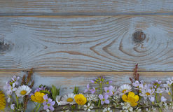 Bunch of fieldflowers,daisies, buttercups, Pentecostal flowers, dandelions on a oldwooden background with empty copy space Stock Image