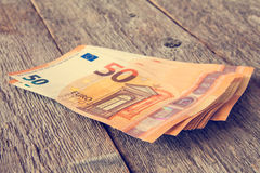 Bunch of fifty Euro banknotes. On wooden background. Filtered image Stock Images
