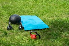 Bunch of fitness training weights on green grass stock photo