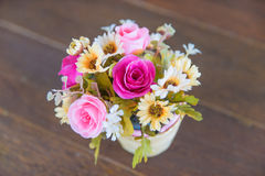 Bunch of flower in a vase is on the wooden floor / specific focus on pink rose. Bunch of flowers in a vase is on the wooden floor / specific focus on pink rose royalty free stock images