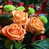 Bunch of flowers. Three orange roses in a bunch with other flowers Stock Images