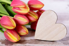 Bunch of flowers as present with carved wooden heart Stock Image