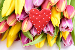 Bunch of flowers as present with red heart Royalty Free Stock Photos