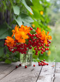 Bunch of flowers and berries in a glass Stock Photo