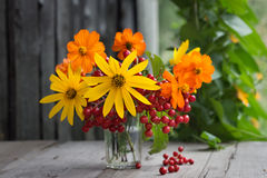Bunch of flowers and berries in a glass Royalty Free Stock Images