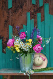 Bunch of flowers in a bucket with pink hat Royalty Free Stock Photo