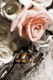 Bunch of flowers and gold rings on old wood Stock Photos