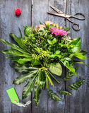 Bunch of flowers making with scissors and blank green card on blue wooden background Stock Photography