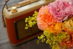 Bunch of flowers, red retro radio on grey background. old retro radio is paired with rose and lady`s mantle on grey floor. Lateral view. Music and nature stock images