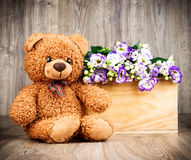 Bunch of flowers and a teddy bear Stock Photo