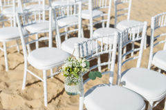 Bunch of flowers in a vase for  wedding ceremony. background  chairs  guests. Stock Image