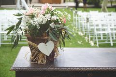 Bunch of flowers on a wooden desk against the white chairs aisle in a wedding celebration. Empty copy space for Editor`s content stock photo