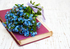 Bunch of forget-me-not flowers and old book Stock Image