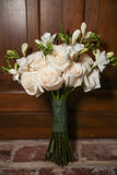 Bunch of freesias and roses. A bunch of freesias, some in bud,  and white roses standing on a brick floor outside a wooden door Stock Photos