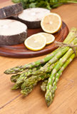 Bunch of fresh asparagus and raw fish Stock Photography