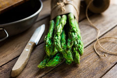 Bunch of fresh asparagus tied with twine, garlic knife kitchenware on wood table, cooking concept Royalty Free Stock Photo