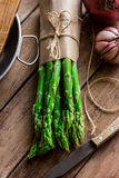 Bunch of fresh asparagus tied with twine, garlic knife kitchenware on wood table, top view Stock Photos